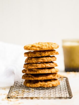 A stack of crisp oatmeal cookies on a vintage cooling rack.