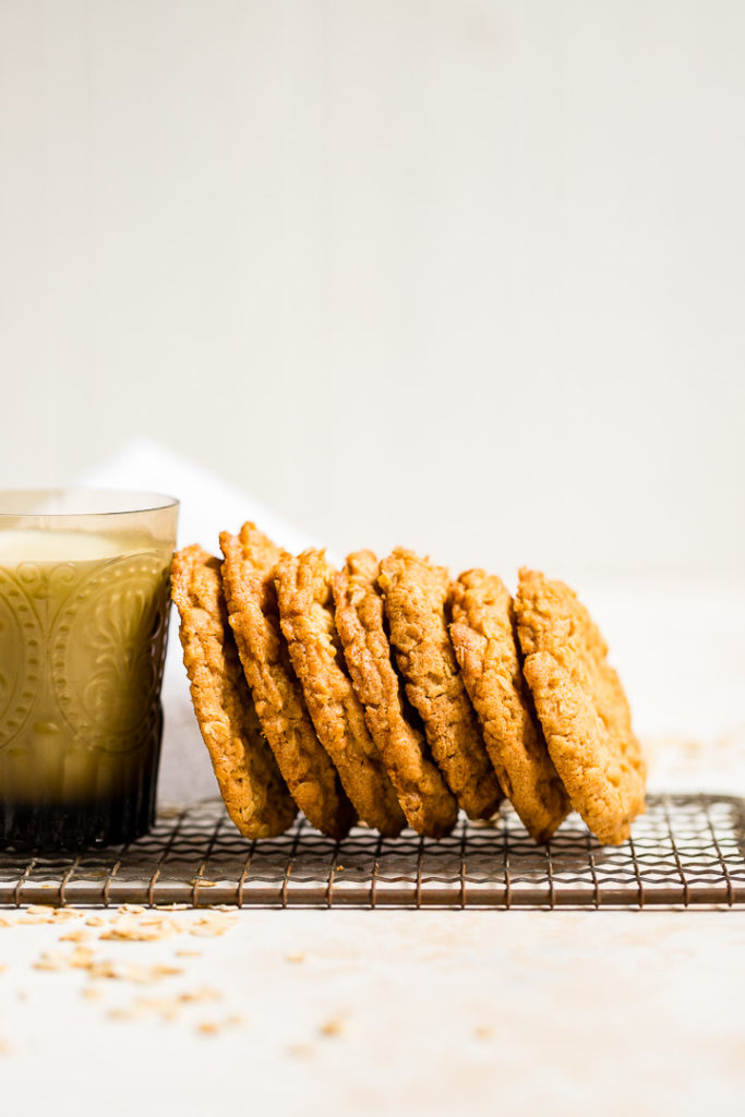 Crisp oatmeal cookies leaning on a glass of milk.