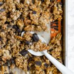 A large baking sheet filled with honey walnut granola with chocolate and cinnamon.