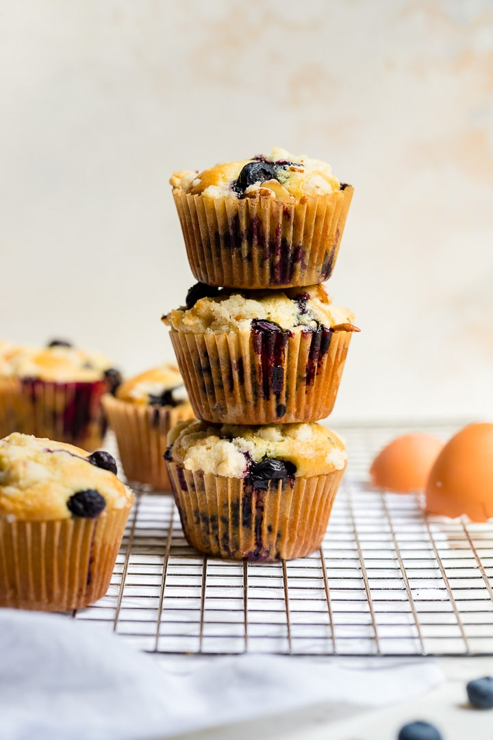 Three blueberry almond muffins with streusel topping stacked on top of one another.