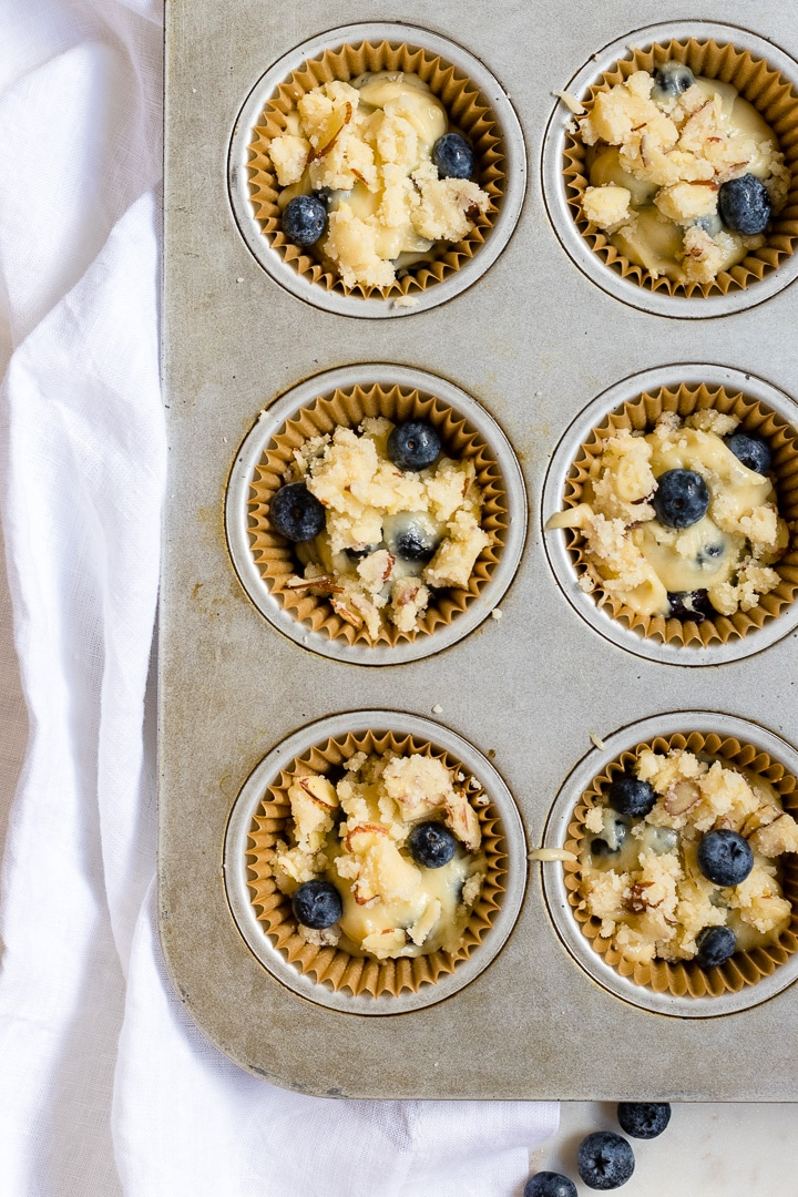 A muffin pan filled with batter for blueberry almond muffins.