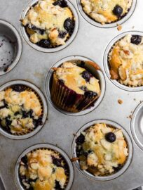 A metal muffin pan filled with just-baked blueberry almond muffins.