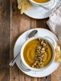 Two bowls of roasted butternut squash soup served with rolls and topped with pumpkin seeds.