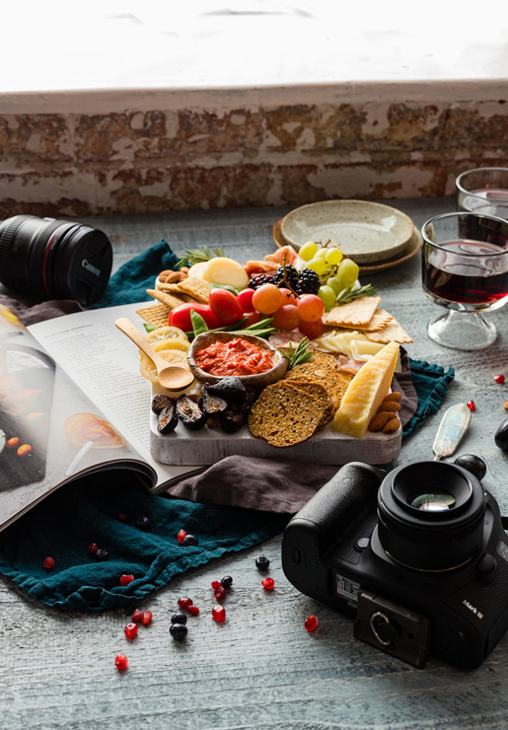 A photography set with a cheese board, open cookbook, glasses of wine, small plates, scattered almonds and other small bites, and Canon camera and lenses.