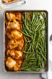 Easy chicken thighs in peanut sauce with green beans, on a sheet pan just out of the oven.