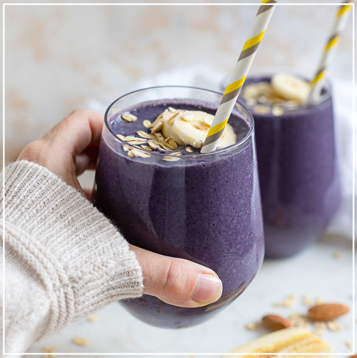 A hand holding a blueberry almond milk smoothie in a small glass with a straw.
