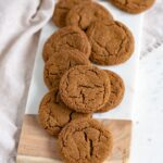A wood and marble cutting board piled high with chewy ginger molasses cookies.