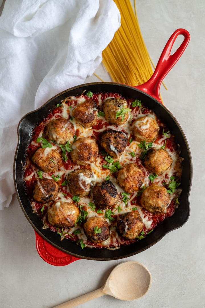 A large red Le Creuset cast iron pan filled with mozzarella-stuffed chicken Parmesan meatballs in marinara.