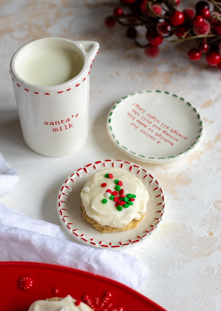 """A sprinkled sugar cookie sitting on a """"For Santa"""" plate with a glass of milk."""