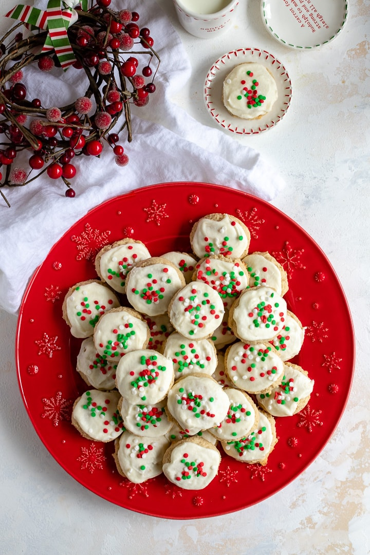 A red holiday plate filled with soft eggnog sugar cookies.