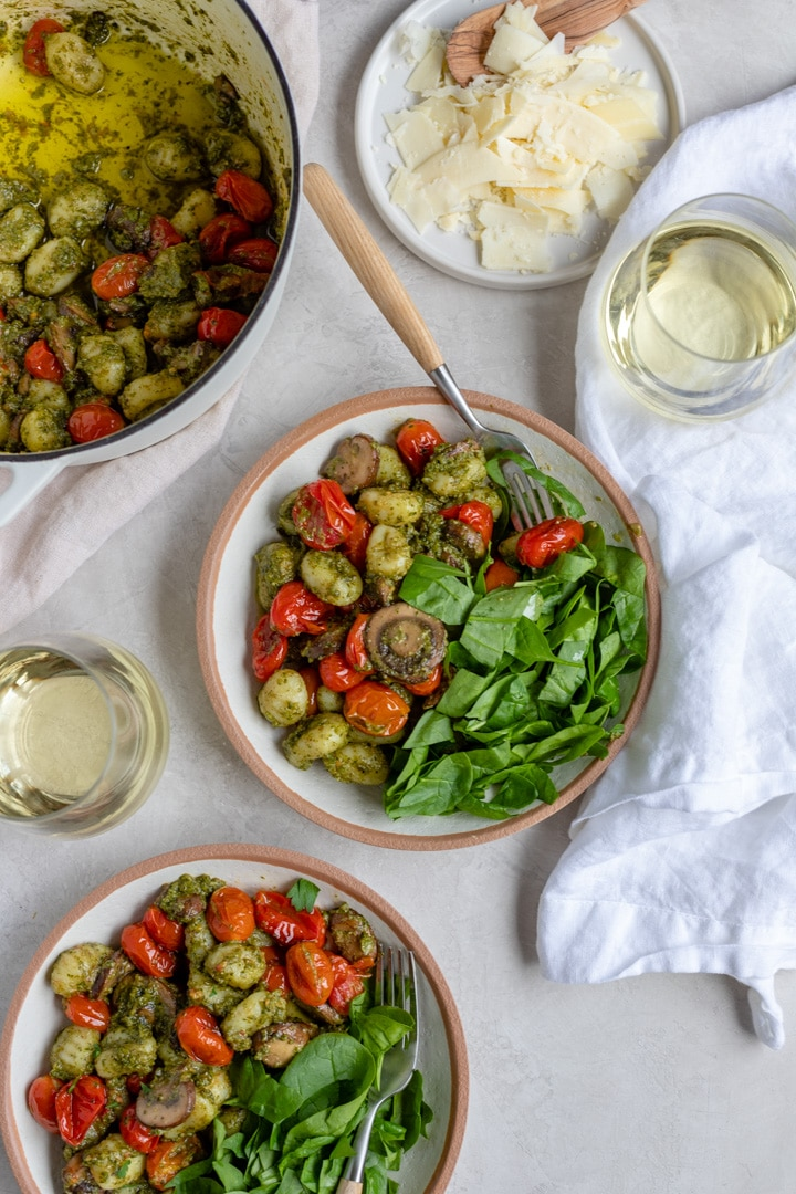 A table set with two bowls of gnocchi with pesto, Parmesan cheese, a side of spinach, and glasses of white wine.