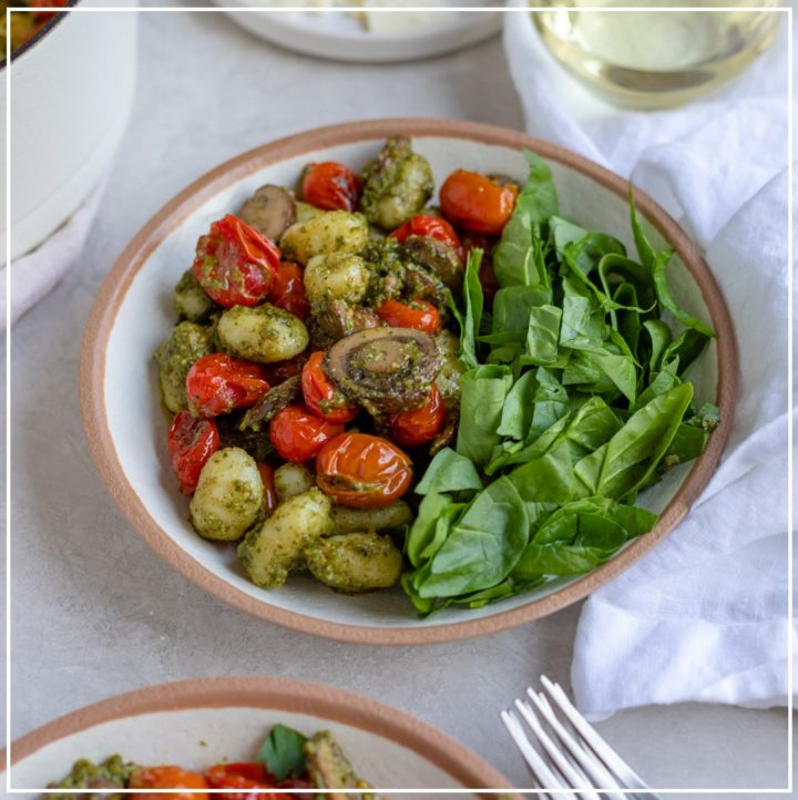 A bowl of gnocchi with pesto and charred cherry tomatoes.