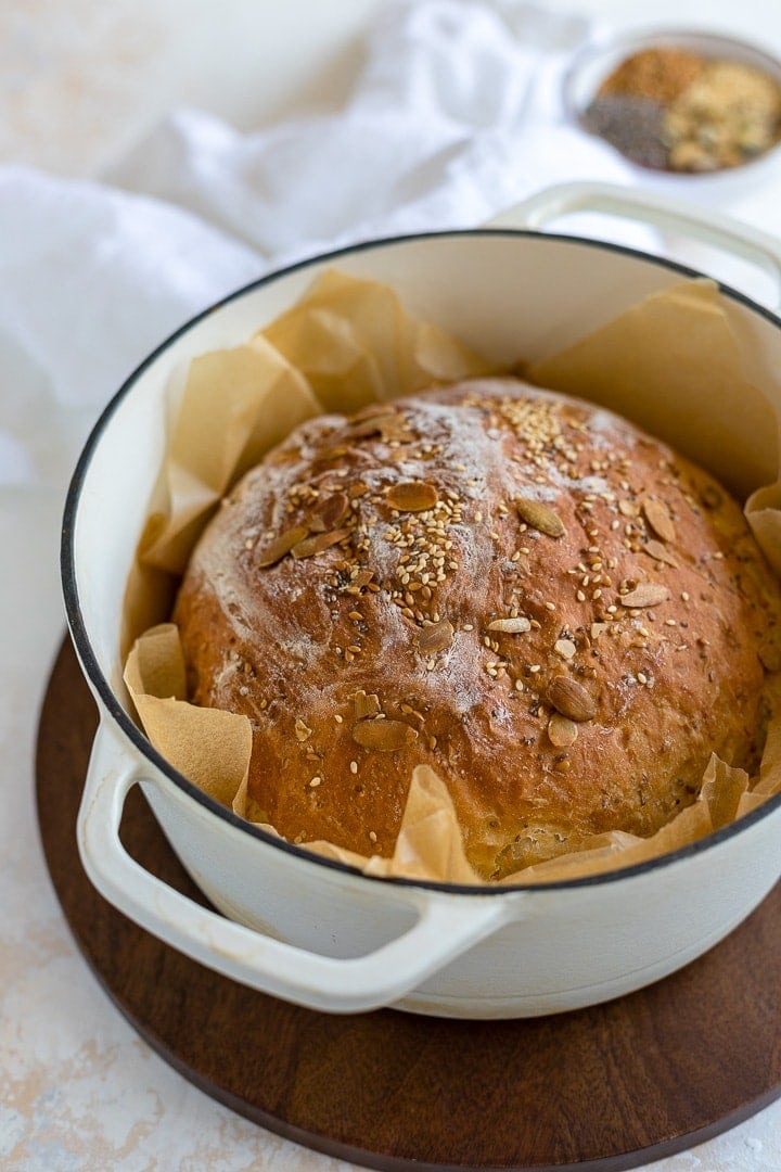 No knead bread with seeds baked in a white Dutch oven.