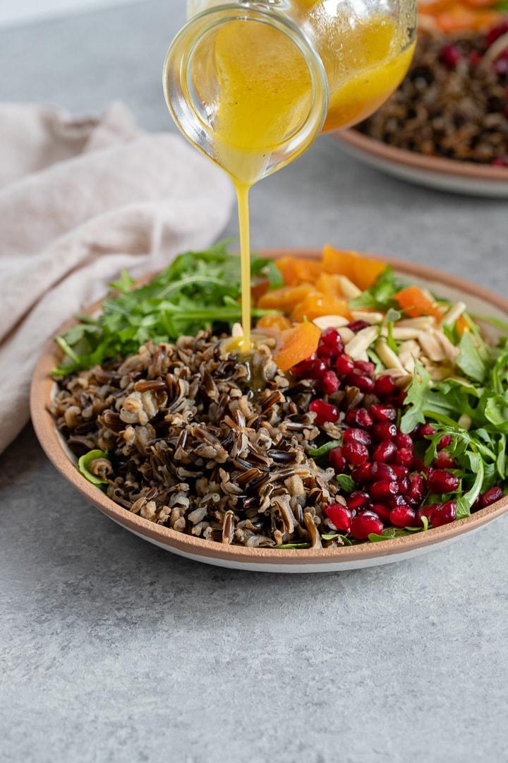 A cruet drizzling white wine vinaigrette onto a wild rice salad.