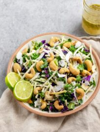 Close-up of a bowl holding cashew coconut slaw with cilantro-lime vinaigrette, made using a Mann's Veggie Blend.