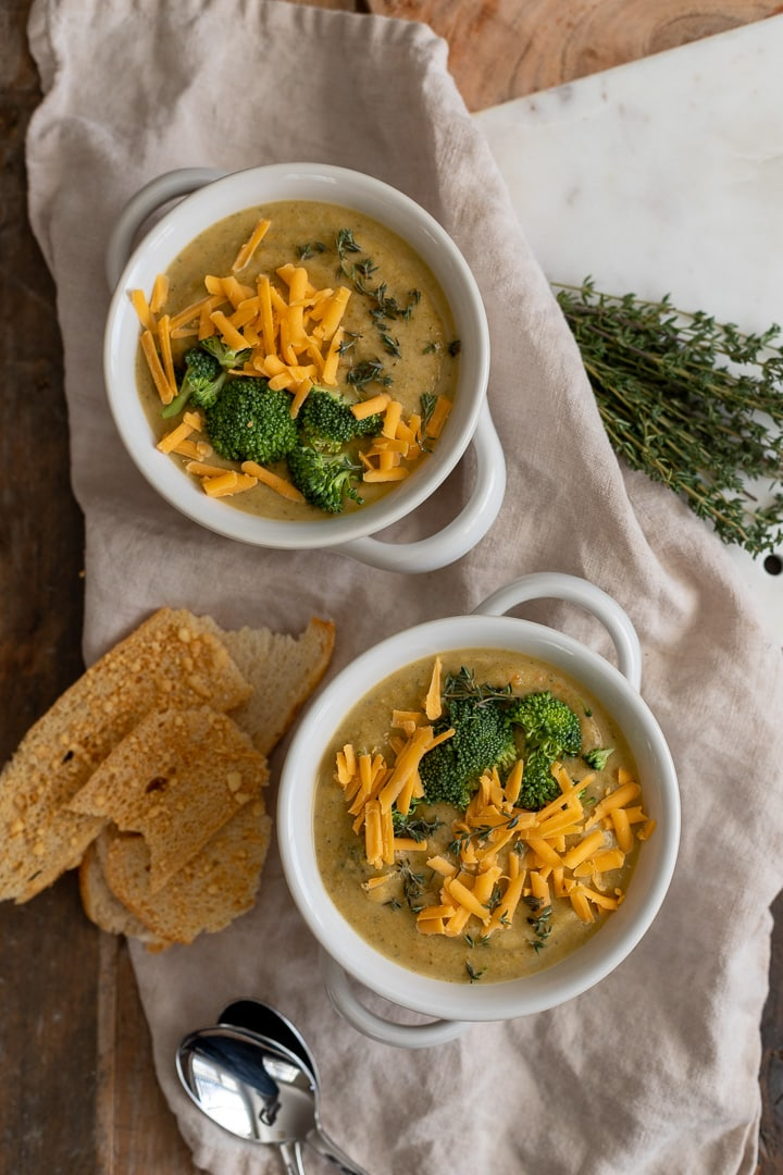 Overhead photo of two bowls containing healthy Instant Pot broccoli cheddar soup.