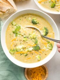 Spoon dipping into a bowl of broccoli cheddar soup.