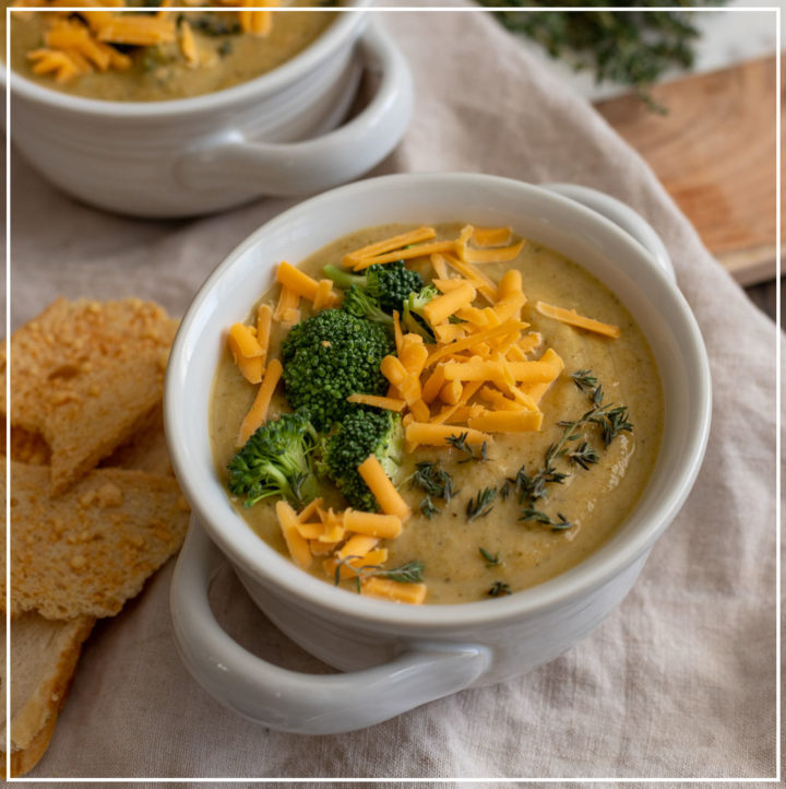 Two bowls of Instant Pot broccoli cheddar soup served with fresh thyme.