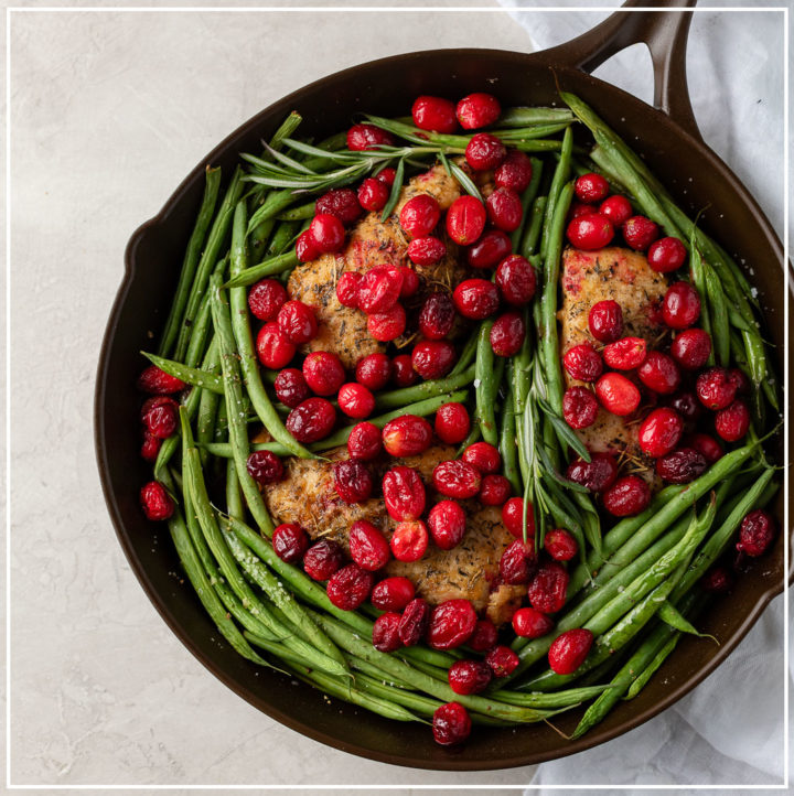 A cast iron skillet holding a meal of balsamic cranberry chicken with green beans, ready to serve.