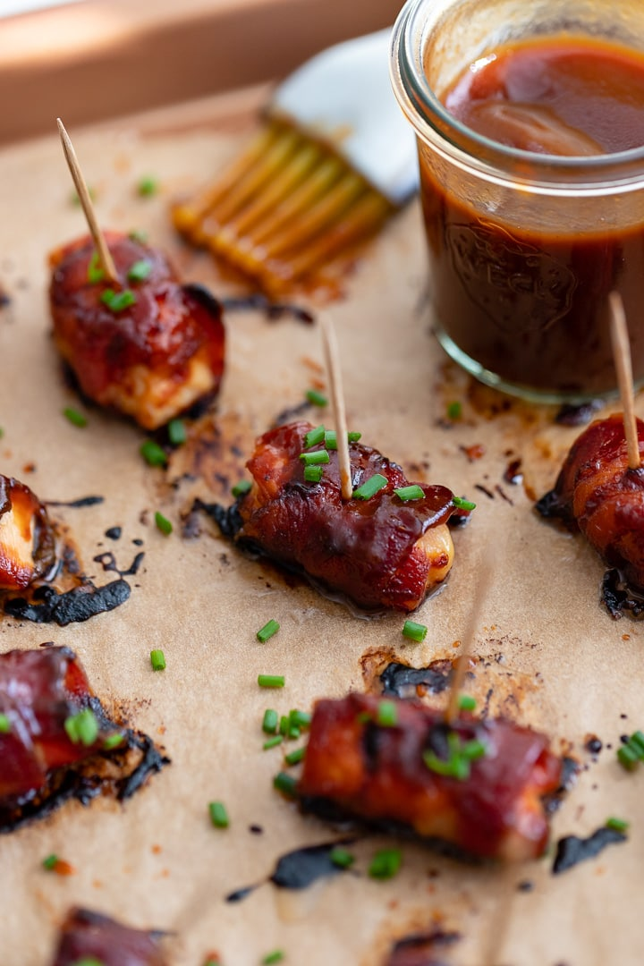 Close up of a chicken bacon BBQ bite slathered in BBQ sauce and garnished with chives.