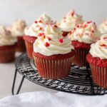 One-bowl red velvet cupcakes, baked and frosted with heart sprinkles, arranged on a black cooling rack.