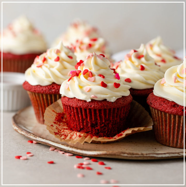 Close-up of an unwrapped red velvet cupcake with cream cheese frosting and heart sprinkles.