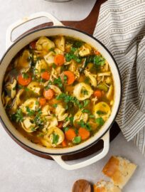 A white Dutch oven filled with tortellini chicken noodle soup.