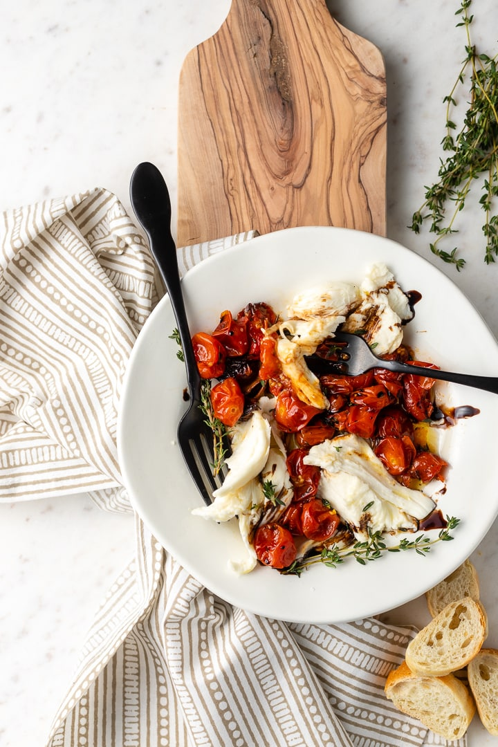 A winter Caprese salad with roasted tomatoes plated with two forks, for sharing!