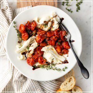 A white plate with a roasted tomato winter Caprese salad on it.