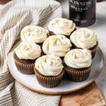 A small plate filled with the best chocolate Guinness cupcakes with Irish cream frosting, with a bottle of Guinness in the background.