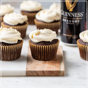 Chocolate Guinness cupcakes with Irish cream frosting arranged on a board.
