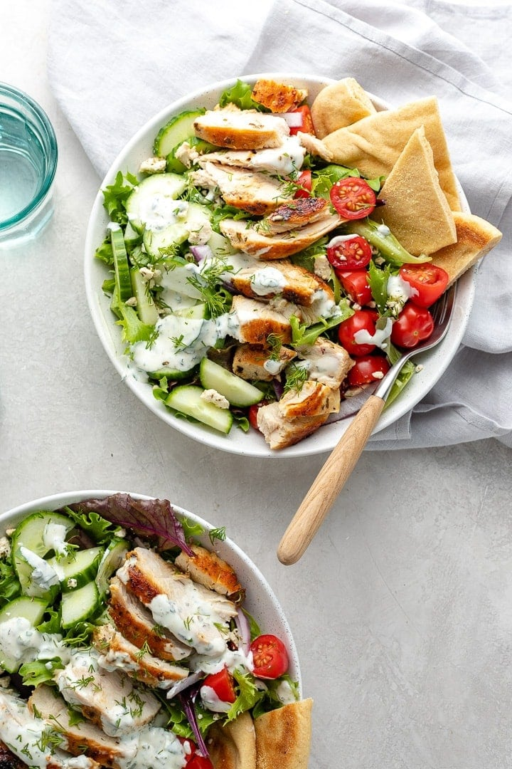 Prepared chicken gyro salad in a bowl with pita wedges and a fork.
