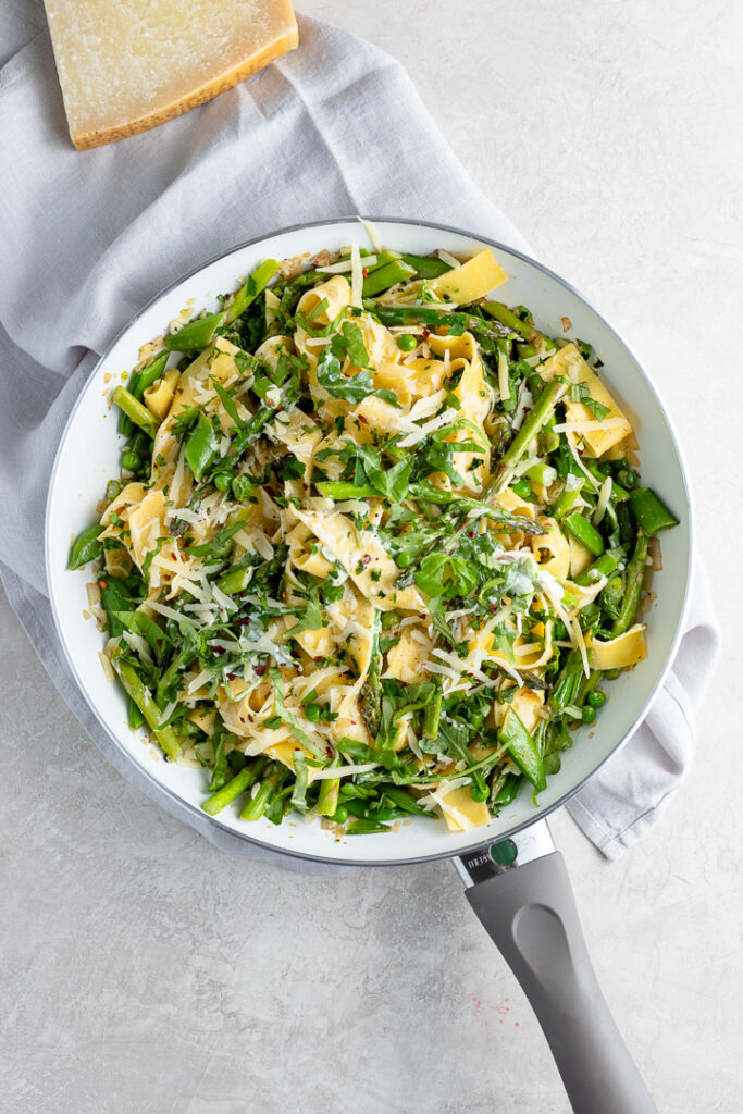 Skillet filled with creamy pasta Primavera.