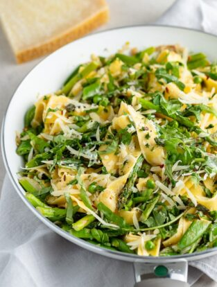 Close up of pasta noodles with spring veggies.