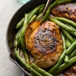 Close-up of honey mustard chicken cooked in a skillet with green beans.