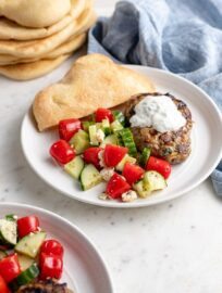 A plate with a Moroccan lamb burger, yogurt sauce, tomato cucumber salad, and fresh pita bread.