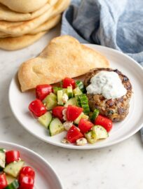 A plate with a Moroccan lamb burger, yogurt sauce, tomato cucumber salad, and fresh pita bread.