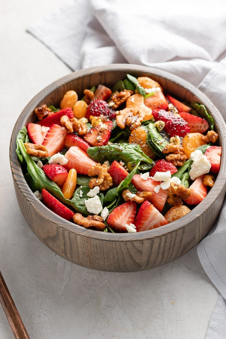 Close up of strawberry spinach salad in a bowl, ready to toss and serve.