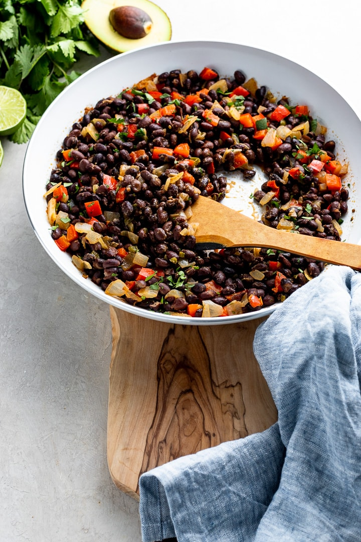 A wooden spoon stirring black beans in a skillet.