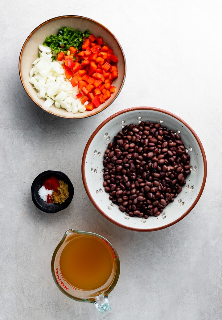 The ingredients for easy spicy black beans: chopped onion, jalapeno, red pepper, canned black beans, chicken or veggie broth, salt and spices.