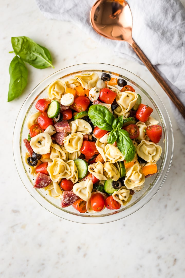Overhead image of a large bowl and serving spoon ready to dish up some Italian pasta salad.
