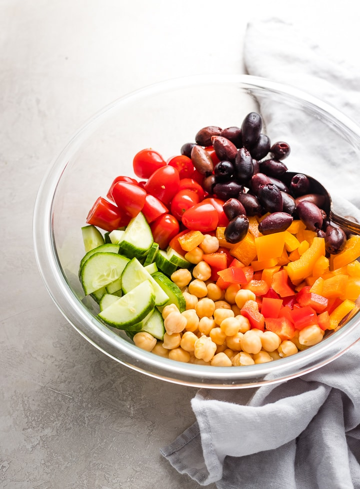 Olives, tomatoes, cucumber, pepper, and chickpeas together in a large prep bowl.