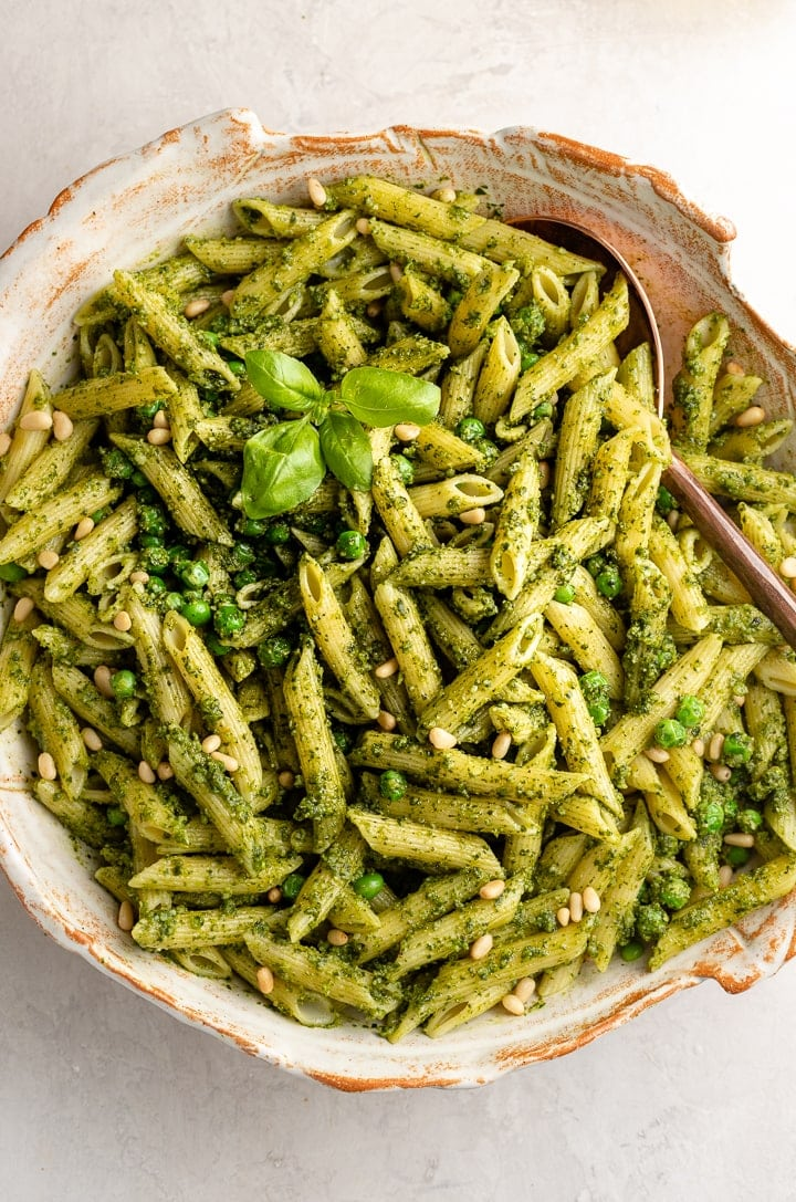 Close up image of penne with pesto and peas.
