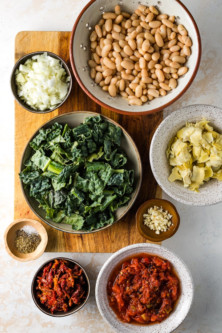 Bowls filled with the ingredients: white beans, kale, onions, artichoke hearts, garlic, diced tomatoes, sun-dried tomatoes, seasoning.