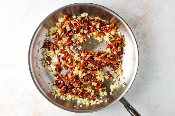 Photo of skillet with sauteed onions, garlic, and sun dried tomatoes.