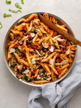 Skillet filled with penne alla vodka with mushrooms and sun-dried tomatoes.