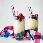 Two glasses filled with layered red, white, and blue frozen lemonade.