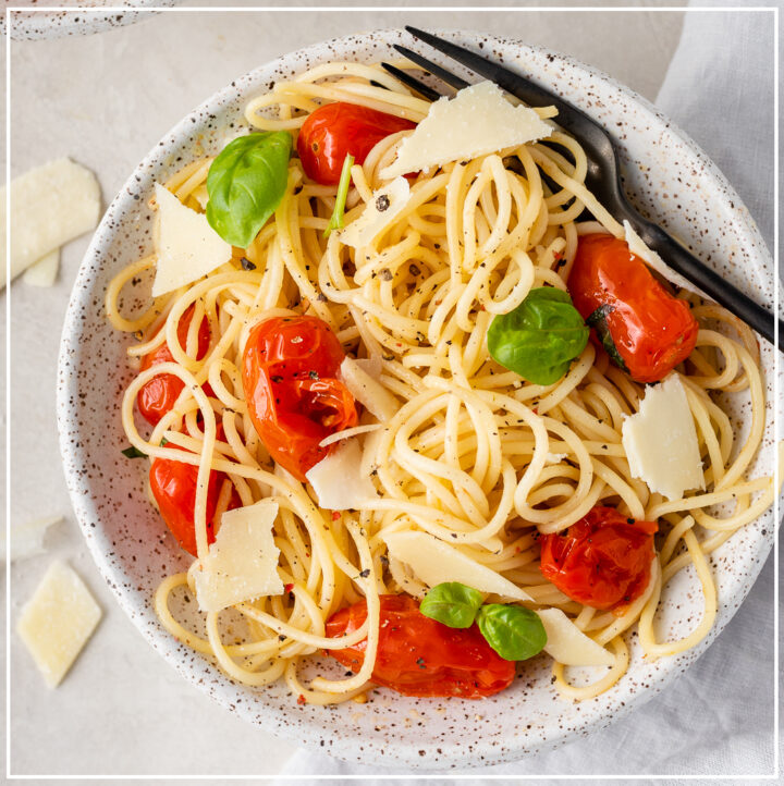 A bowl of roasted tomato and garlic spaghetti, ready to eat.