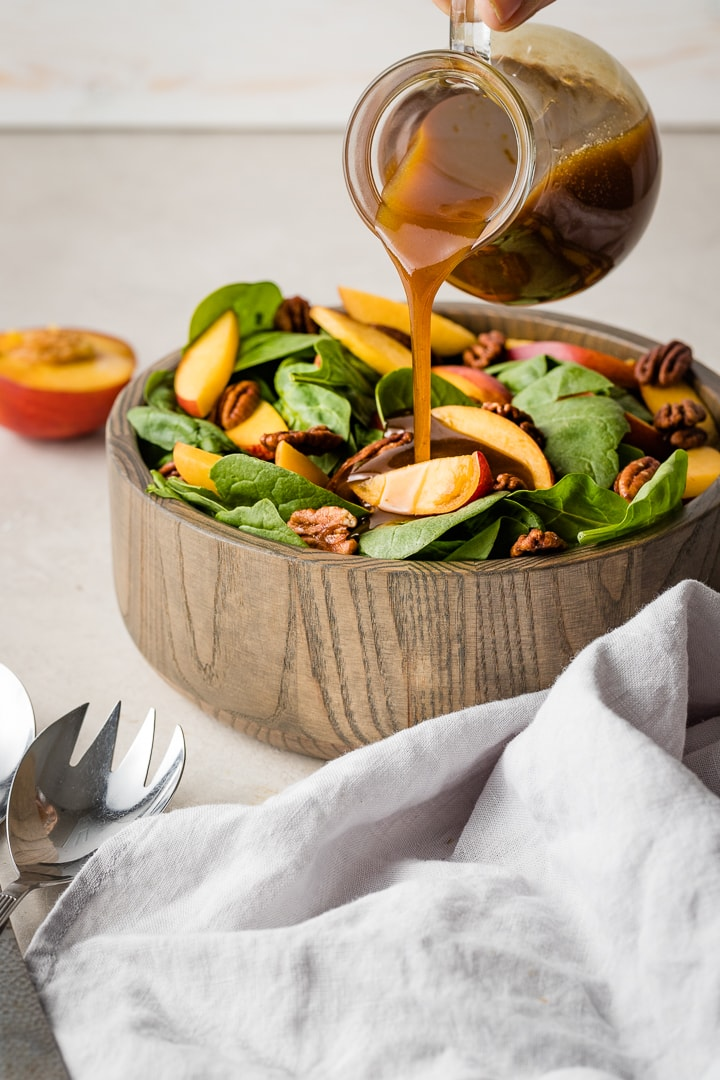Close up image of a mustard balsamic vinaigrette dressing being poured on a spinach salad.