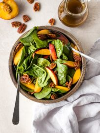 A bowl of spinach salad with nectarines and pecans.